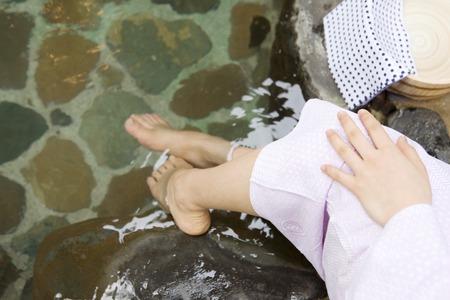 openair: Feet of women soak your feet on the open-air bath Stock Photo