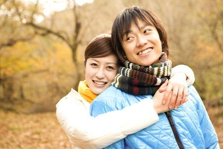 Woman hugging from behind boyfriend