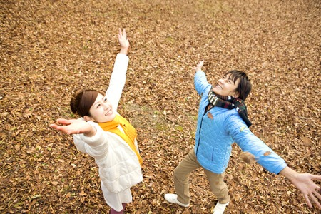 to toss: Couples toss the fallen leaves Stock Photo