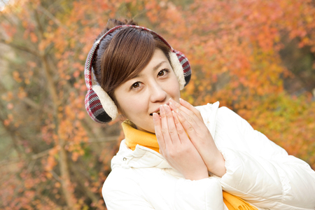 earmuff: Women who are warm and exhaling in hand Stock Photo