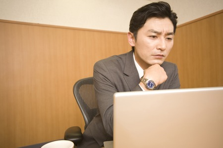 about: Businessman to think while watching the PC Stock Photo