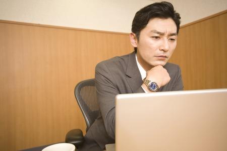 PC を見ながら考えるビジネスマン