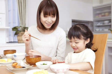 Moeder om te leren hoe je eetstokjes en dochter gebruiken om ernaar te luisteren