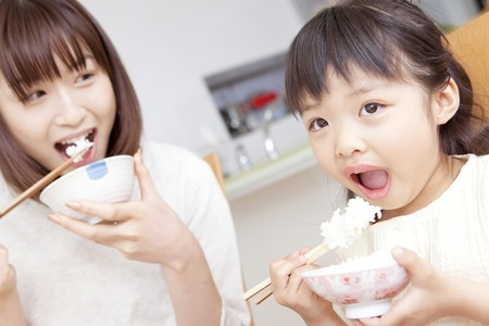 cereal: Mother and daughter to eat rice Stock Photo
