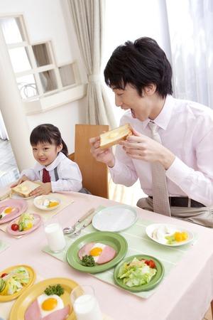niños desayunando: Los hombres y las mujeres comen la tostada