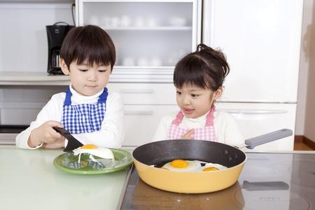 男の子と女の子は、皿に目玉焼きを転送するそれを見る