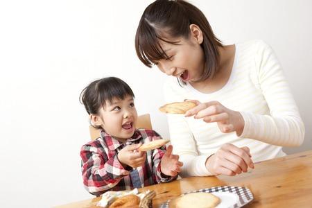 Las niñas y las mujeres que comen una galleta