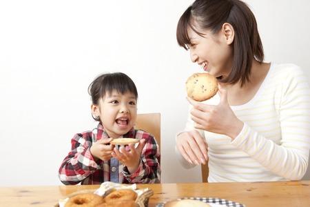 女の子とクッキーを食べる女性