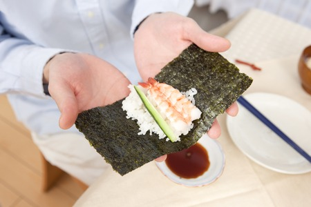 dry provisions: Hand of man to create a hand-rolled sushi