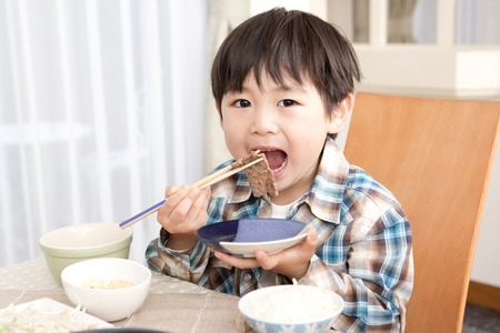 肉を食べる少年 写真素材