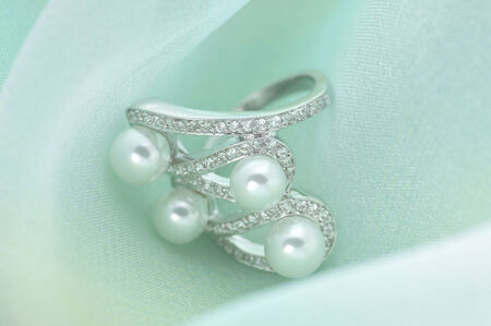 gorgeousness: The accessory made by silver and peals on the white cloth.