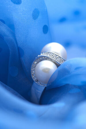 gorgeousness: The accessory made by silver and peals on the blue fabric. Stock Photo