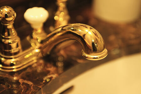 powder room: The sink with a gold faucet.