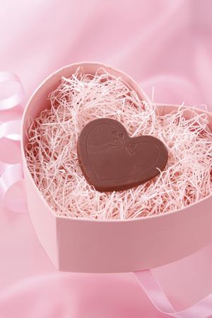 A heart chocolate in the heart box on the pink cloth. Stock Photo - 6804627