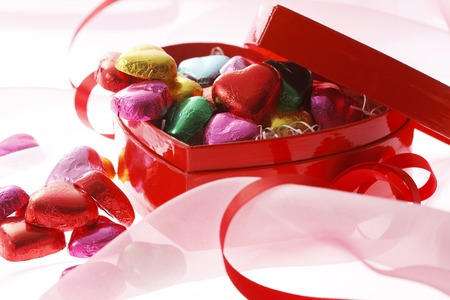 Some heart chocolate in the red heart box and red ribbon. photo
