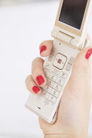 女性と携帯電話のマニキュア 写真素材