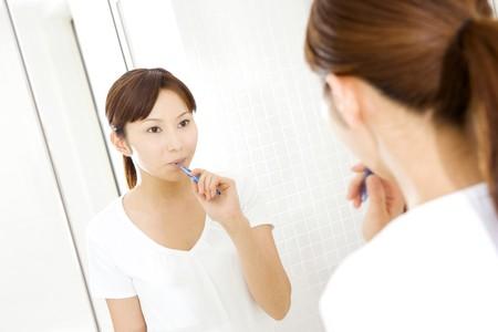Japanese woman brushing teeth photo