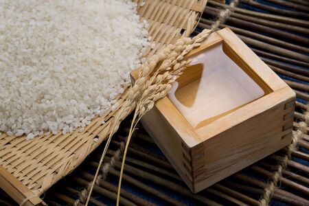 japanes: The measuring cup of Japanese sake with rice ears and rice on the basket