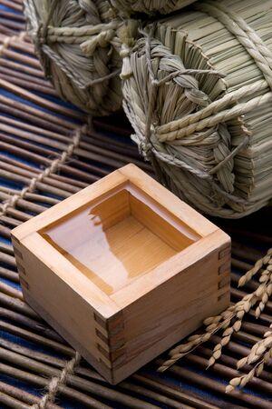 sake: Medici�n de la taza de sake y bolsas de paja de arroz de madera Foto de archivo
