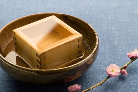 sake: Una taza de cuadrados madera de sake en la cer�mica con flores de color rosa de ciruela