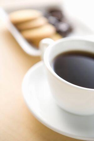 一杯のコーヒーと木製のテーブルの上のクッキーの