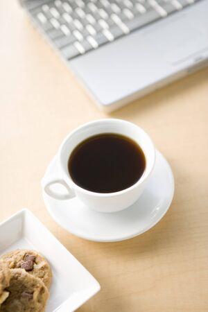 一杯のコーヒーと木製のテーブルに PC でクッキーの