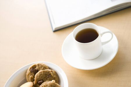 コーヒーとクッキーで木製のテーブルの上の本の白いカップ