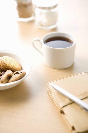 白いカップのコーヒーとクッキーの木製のテーブルの上
