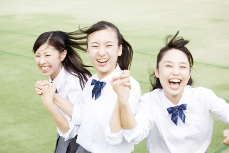 frolic: High school girls to frolic hold hands Stock Photo