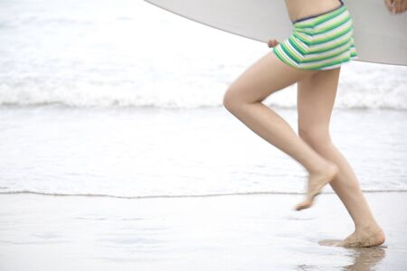 Feet of swimsuit woman running with a surfboard