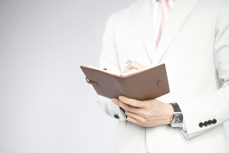 article of clothing: Businessman write something in notebook Stock Photo