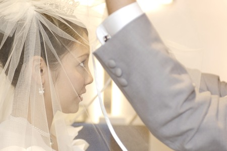 asian ancestry: Groom to raise the wedding veil Stock Photo
