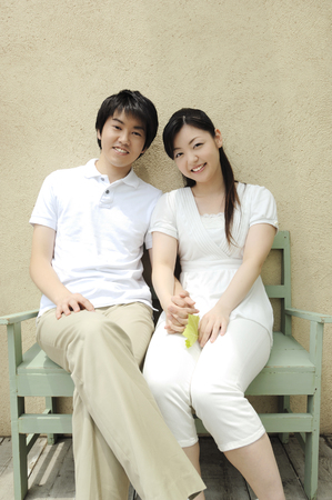 he laughs: Couple sitting on a bench