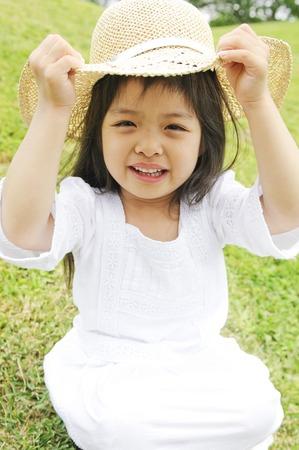 chapeau de paille: Jeune fille tenant un chapeau de paille Banque d'images