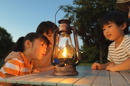 Mother and brother and sister stare light of the lantern