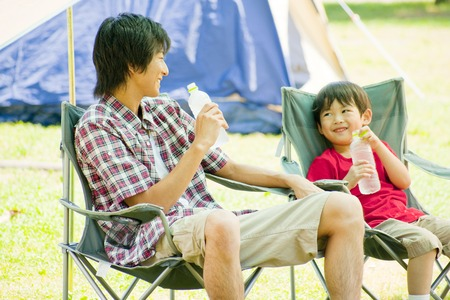 rehydration: Father and son chatting sitting in a chair in the camping Stock Photo