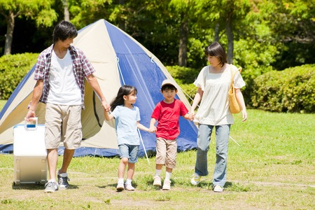 Family walking hand in hand by the camp site 스톡 콘텐츠