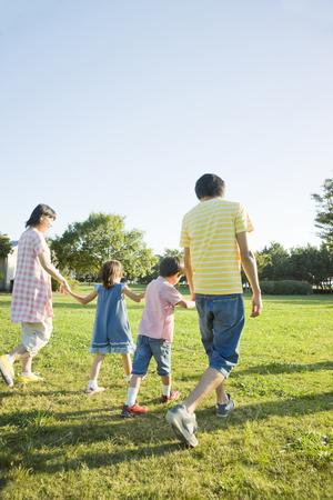 手をつないで公園を散歩する家族の背面図