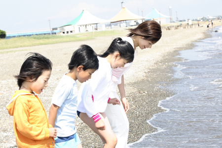 asian natural: Mother and children put a foot on the sea