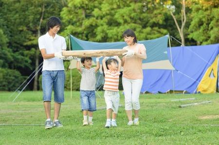 Draag het hout voor het kampvuur familie Stockfoto