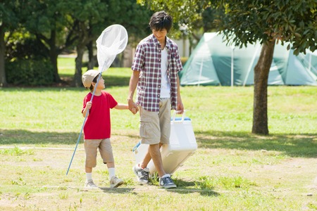 campsite: Father and son walk hand in hand the campsite