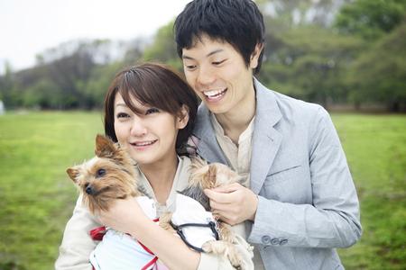 子犬とのカップル 写真素材