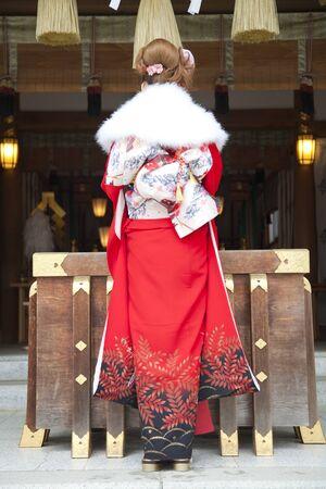 early 20s: Rear View of female kimono figure to pray