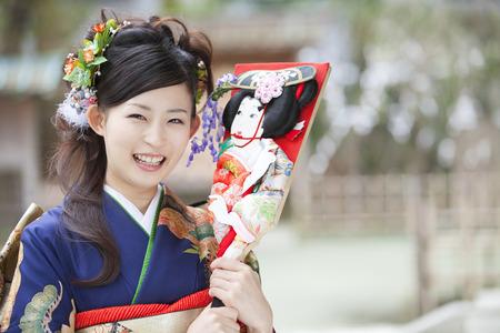 battledore: Woman of kimono wearing smiling with a battledore