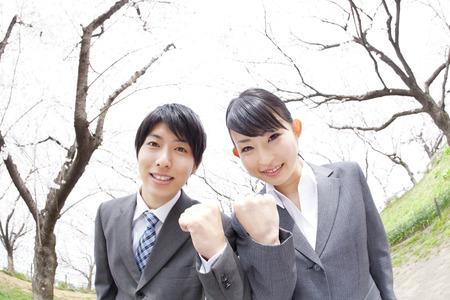 桜の木の下でガッツポーズするビジネスマン 写真素材