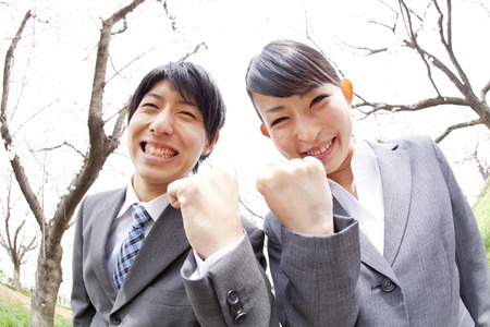 Businessman and OL to take guts pose under the cherry tree Stock Photo