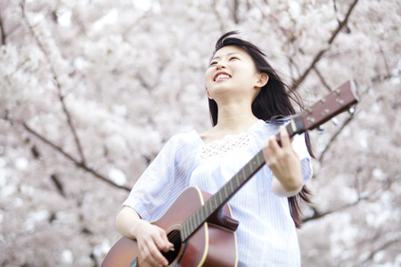 early 20s: Woman to play guitar under the cherry tree