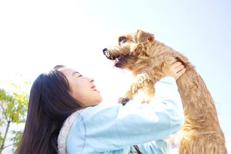 Girl to high high the Norfolk terrier outside