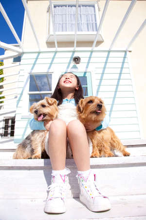between: Girl sitting with two animals Norfolk terrier on the terrace