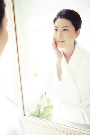 house robe: Women look in mirror Stock Photo